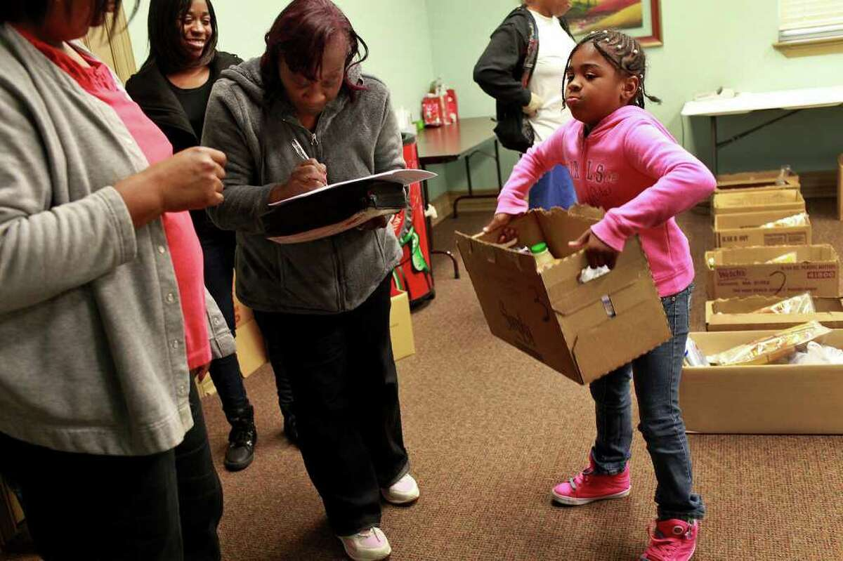 Nivea Shelton, 8, holds a box of food for her family including her mother, Veronica McCurtis, far left, while Pamela Moore, center/left, signs for her box of food with a member of Lively Stone Church Food Ministry, Barbara Gay, left, as the ministry holds a food distribution with the Merced Housing Texas program at Artisan at Willow Springs apartments in San Antonio on Saturday, Dec. 17, 2011.