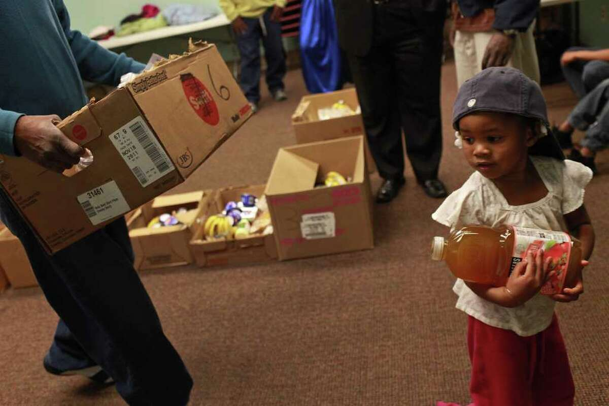 Nihyana Hamilton, 3, helps her father, Peter Hamilton, left, carry food given to them by the Lively Stone Church Food Ministry which holds a food distribution every third Saturday with the Merced Housing Texas program at Artisan at Willow Springs apartments in San Antonio on Saturday, Dec. 17, 2011.