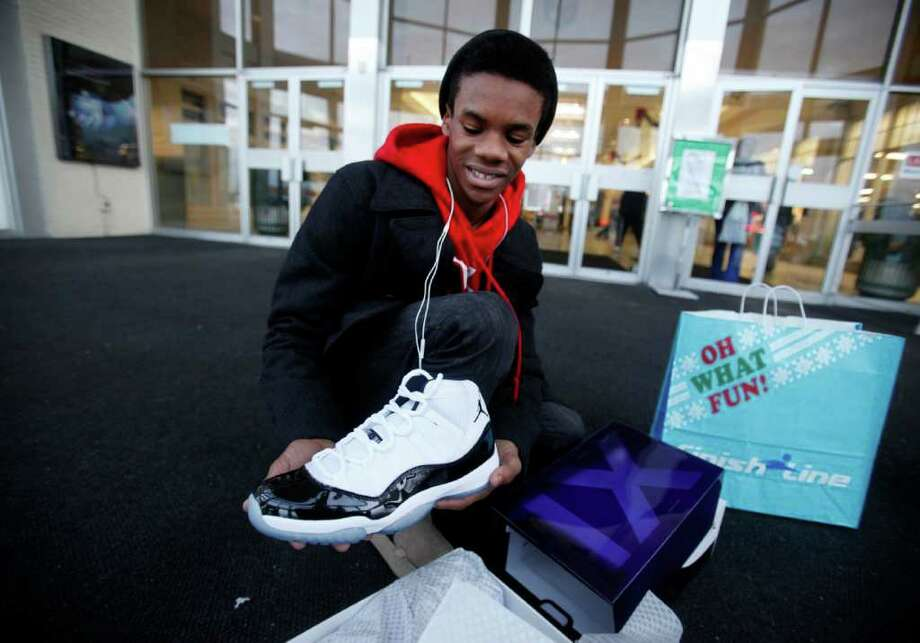 Kristopher Rush, 14, shows off the Nike Air Jordan shoes he got for Christmas from his parents Friday, Dec. 23, 2011, outside the Lafayette Square Mall in Indianapolis, where he waited in line with his father and brother for over three hours. Police were called in to control crowds of shoppers flocking Lafayette Square and Castleton Square malls in Indianapolis to control the crowds waiting for the shoes. The release of Nike's retro Air Jordans caused a frenzy at stores across the nation early Friday, with hundreds of people lining up for a chance to buy the classic basketball shoes and rowdy crowds breaking down doors and starting fights in at least two cities. AP Photo/The Indianapolis Star, Danese Kenon)  NO SALES Photo: Danese Kenon / The Indianapolis Star