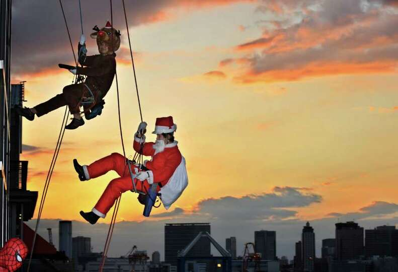 Workers in a Santa Claus (bottom) and a reindeer costume clean windows outside of a 31-meter-high bu