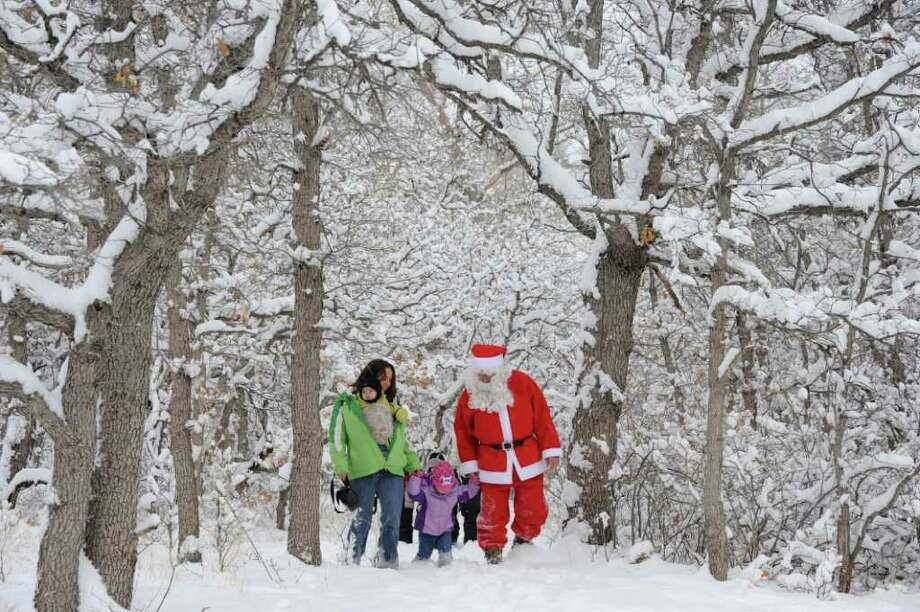 "Kaylee Vasquez, left, and her children Killian, 6 months, and Annya, 2, make their way through fresh snow near the Bear Creek Nature Center in Colorado Springs, Colo., during a ""Hike With Santa"" sponsored by the center. Photo: Mark Reis, Associated Press / The Colorado Springs Gazette"