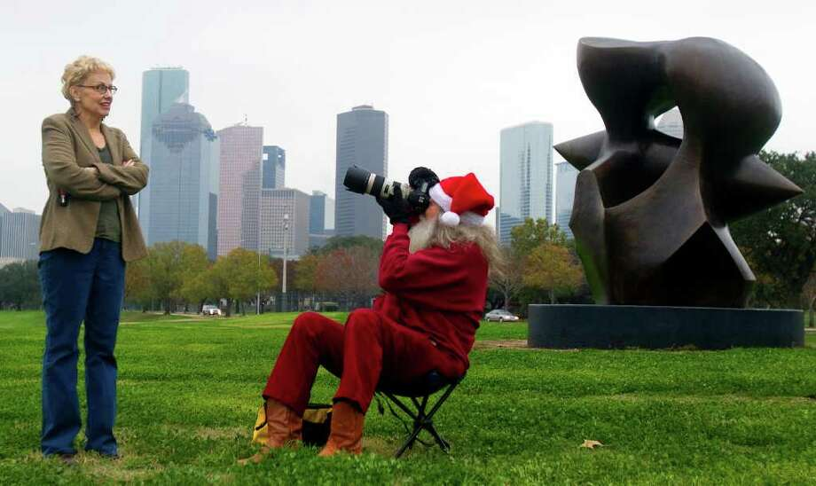 "A man that calls himself ""Santa,"" takes a photo of a curious passerby Kathy Gentry, along Buffalo Bayou Park Friday, Dec. 23, 2011, in Houston. Gentry stopped because she was curious why he was taking photos because she sees him almost everyday. Santa was inspired by a story of a geologist that took a photo of a scene in the Mojave Desert everyday for 30 years. After hearing the story, Santa thought ""I could do that."" He has taken photos off and on at the scene since 2004. Photo: Cody Duty, Houston Chronicle / © 2011 Houston Chronicle"