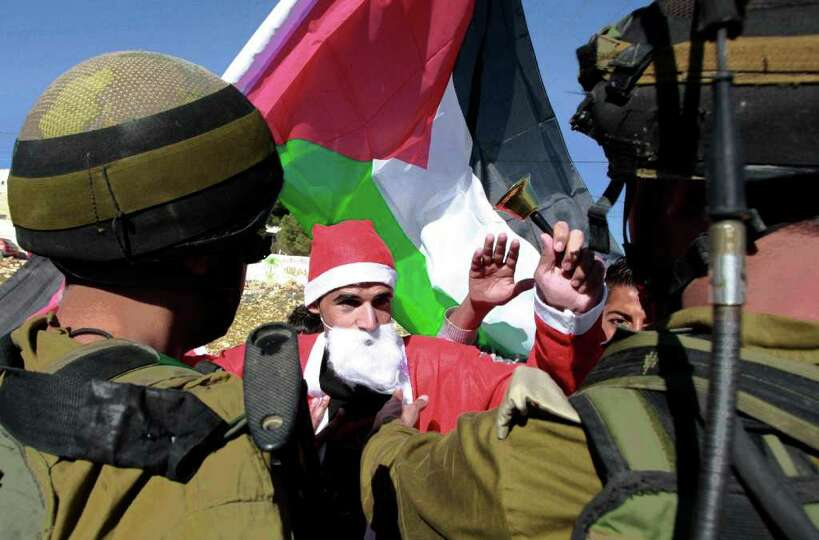 Israeli soldiers push a Palestinian protestor dressed as Santa Claus who also holds a Palestinian fl