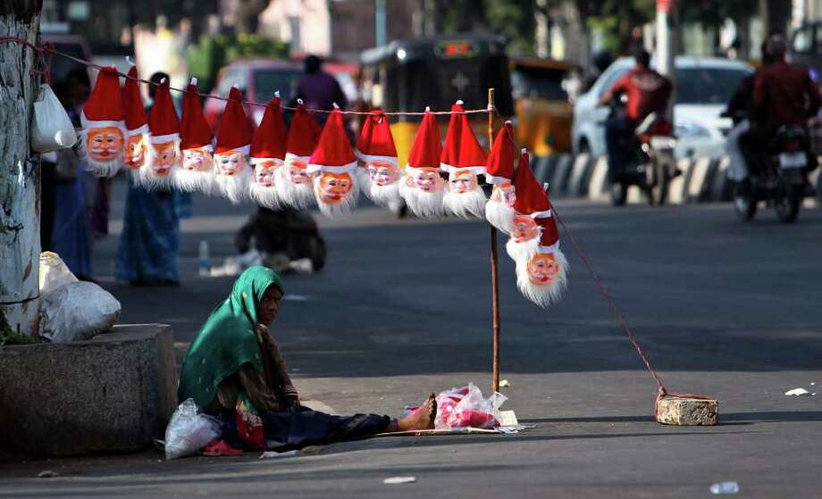 An Indian street vendor selling Santa Claus masks waits for customers ahead of Christmas on a road in Hyderabad, India, Friday, Dec.23, 2011. Christmas day is observed as a national holiday in India. Photo: Mahesh Kumar A, Associated Press / AP