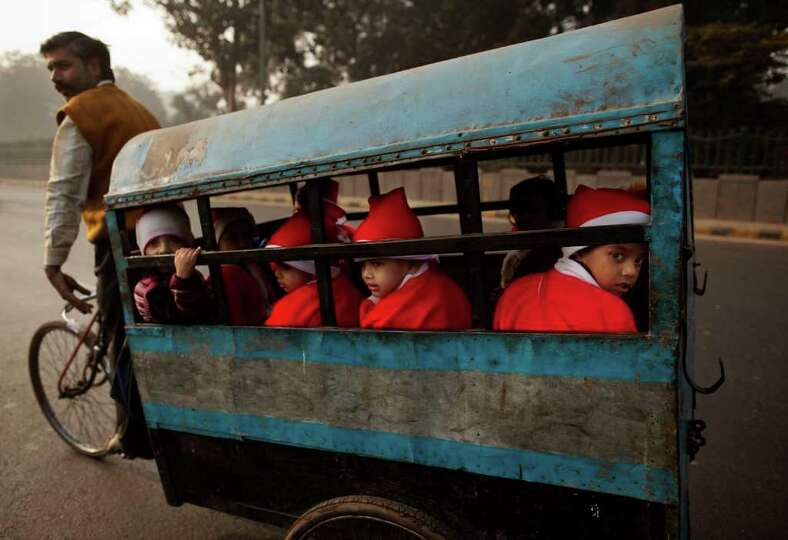 Indian children wearing festive clothing ride in the back of a bicycle rickshaw on their way to a Ch