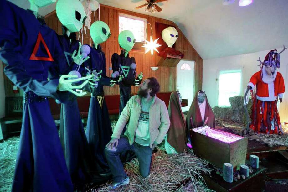 "Portland artist Matt Henderson kneels in front of his  ""Alien Nativity"" exhibit Thursday, Dec. 22, 2011, in Portland, Ore. A former NE Portland church is decked out this holiday season for a 3-D journey that is, intentionally, confusing and provocative. Henderson has created an odd twist on nativity scenes - one that replaces the three wise men with four aliens and also includes a Santa Claus as a shaman, complete with a deer's skull carrying antlers. Photo: Rick Bowmer, Associated Press / AP"