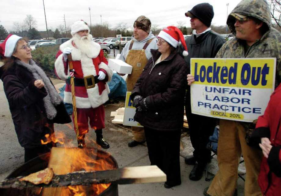 Karl Stahl, who dresses as Santa at the Findlay Village Mall, talks with the locked out picketers from Cooper Tire in Findlay, Ohio, on Friday, Dec. 23, 2011. Stahl brought doughnuts supplied by Fort Findlay Coffee & Doughnut Shop to show support for the workers. Photo: Randy Roberts, Associated Press / The (Findlay) Courier