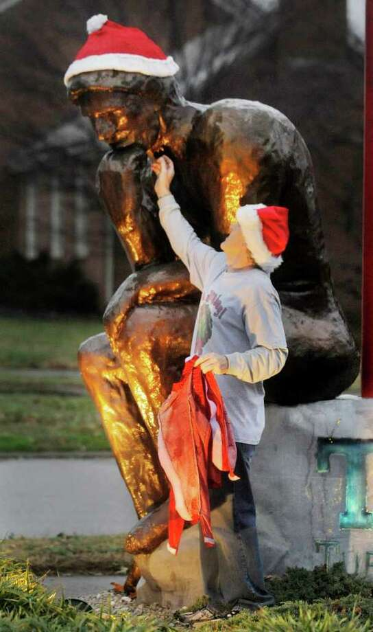 "Owner Tom Deyton removes a Santa hat from ""The Thinker"" statue Thursday, Dec. 22, 2011 before closing time at T.D.'s Tuff Decisions in Owensboro, Ky. The reproduction of Auguste Rodin's sculpture is in front of the costume rental store. Photo: John Dunham, Associated Press / (c) 2011"