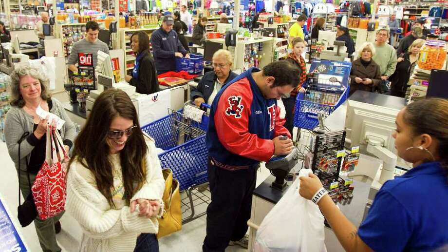 Nick de la Torre Photos : Chronicle BRISK BUSINESS: Mario Rodriguez of Houston, center, was among dozens of shoppers on Friday at Academy's Southwest Freeway store. Retailers also are expecting a busy Monday. Photo: Nick De La Torre / © 2011  Houston Chronicle