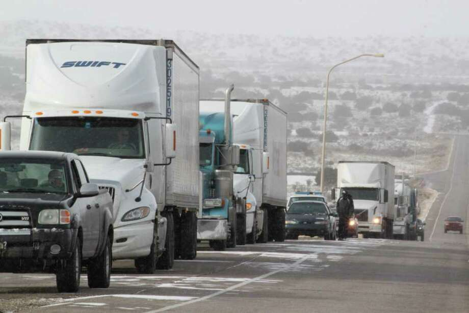 Dozens of vehicles sit along the side of a highway in Rio Rancho, N.M., waiting for authorities to reopen U.S. 550 northbound on Friday, Dec. 23, 2011. Another blast of winter weather has socked New Mexico, closing parts of major highways and canceling flights for holiday travelers. Heavy snow and high winds struck the region late Thursday and forced dozens of holiday motorists in western New Mexico off Interstate 40 after conditions made driving near impossible.  (AP Photo/Susan Montoya Bryan) Photo: Susan Montoya Bryan / AP