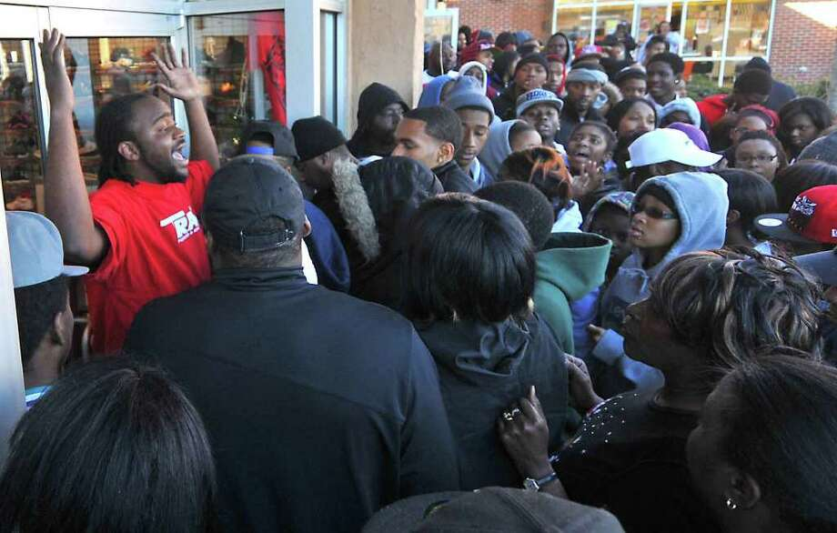 "A store employee pleads with a crowd waiting to buy Nike's newly released Air Jordan 11 Retro Concords to ""back up"" outside the Trax shoe store Charlotte, N.C. Friday, Dec. 23, 2011. The release of the new basketball shoes caused a frenzy at stores across the nation Friday as scuffles broke out and police were brought in to stamp out unrest that nearly turned into riots in some places. Photo: Todd Sumlin, Associated Press / The Charlotte Observer"