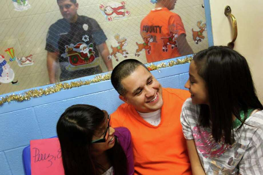 "Eugene ""Geno"" Perez, 39, most recently arrested on drug charges, greets his daughters who are 13 and 12, as he arrives at the annual Christmas celebration for Papas and Their Children, at the Bexar County Jail Annex, Thursday, December 15, 2011. This will be Perez's third Christmas in jail. PATCH has been hosting Christmas for incarcerated fathers and their children at the Bexar County Jail since 1993. Inmates who maintain good behavior and are accepted in the PATCH program attend numerous parenting classes and, in return, earn a one-hour visit with their child or children bi-monthly. Photo: JENNIFER WHITNEY, Jennifer Whitney/ Special To The Express-News / special to the Express-News"