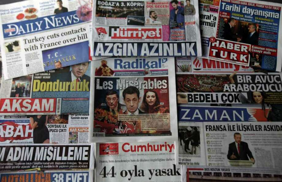 """The headlines of some Turkish newspapers in Turkish, French and English, all condemning the French National Assembly's Thursday bill, which would see anyone in France who publicly denies the 1915 Armenian genocide face a year in jail and a fine of 45,000 euros ($58,000) , in Ankara, Turkey, Friday, Dec. 23, 2011. Turkey is recalling its ambassador to France and halting official contacts in retaliation for  French Parliament's vote making it a crime to deny the WWI-era mass killings of Armenians was a genocide. Hesadlines read: """" Crazy minority ( of French lawmakers), high price will be paid, doors closed, we have frozen and 38 stupid votes"""" (AP Photo/Burhan Ozbilici) Photo: Burhan Ozbilici / AP"""