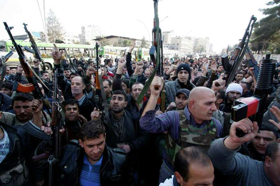 MUZAFFAR SALMAN : ASSOCIATED PRESS SUICIDE BOMBERS: Members of Syrian security chant slogans Friday at the site of suicide bombings in Damascus. At least 30 people died in the brazen attack on government buildings. Photo: Muzaffar Salman / AP