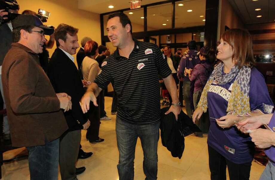 The Washington Huskies football head coach Steve Sarkisian (center) leads the team into the Marriott Rivercenter Hotel as the team gets greeted by mariachis and fans as they arrive in San Antonio on Friday, Dec. 23, 2011. The Huskies will play Baylor in the 2011 Valero Alamo Bowl on Dec. 29. Kin Man Hui/kmhui@express-news.net Photo: Kin Man Hui, SAN ANTONIO EXPRESS-NEWS / San Antonio Express-News