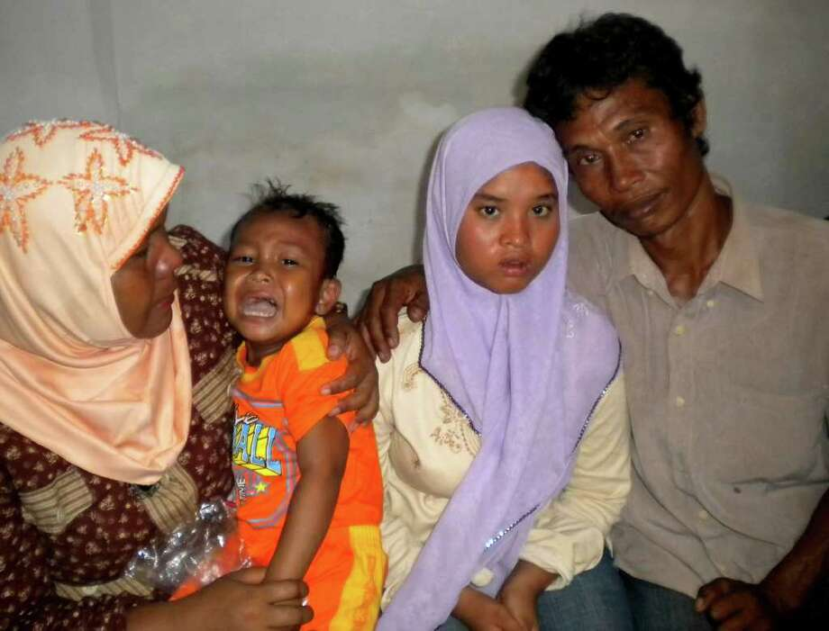 ASSOCIATED PRESS HOMECOMING: Fifteen-year-old Meri, second from right, was reunited with father Yusuf, mother Yusniar, left, and brother Aris in Indonesia's seven years after the deadly tsunami. / AP