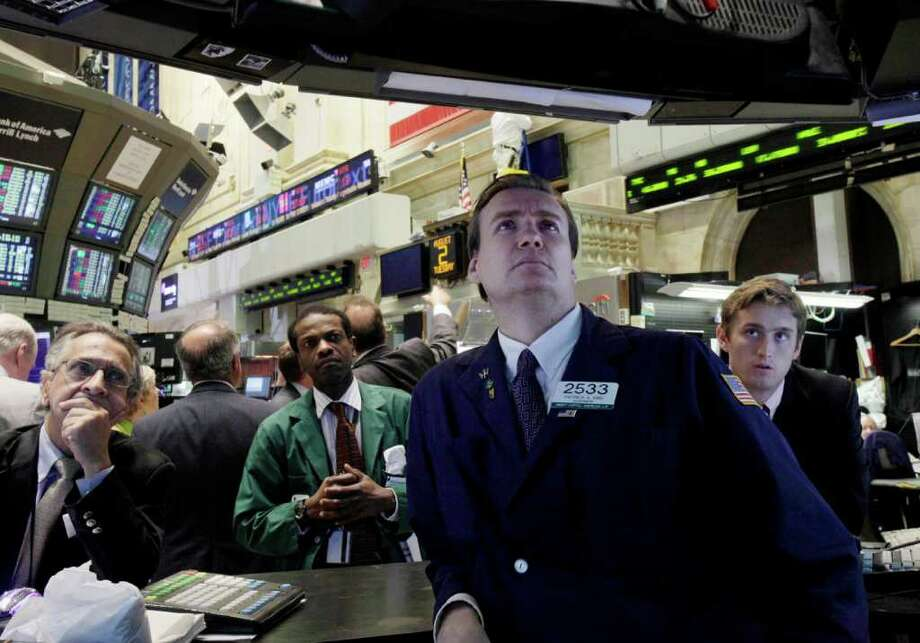FILE - In this Aug. 2, 2011 file photo, specialist Patrick King, second from right, and others watch President Barack Obama's remarks on a television monitor the floor of the New York Stock Exchange. The good news is that Wall Street experts think stock prices will rise by more than 10 percent in the coming year. The bad news is they expected big gains in 2011 and got nearly zero instead.(AP Photo/Richard Drew, File) Photo: Richard Drew