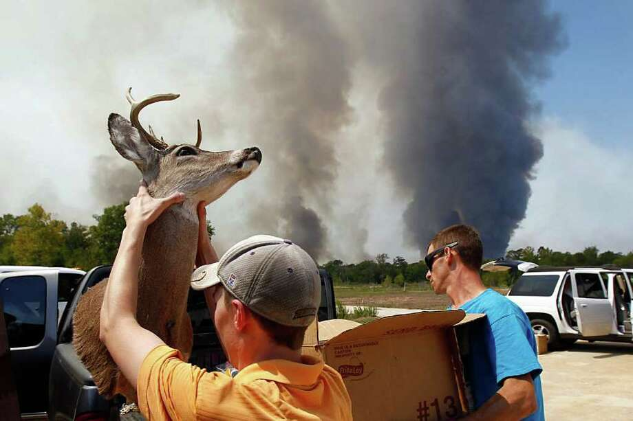 Sept. 6, 2011 | David Courtney, front, and his friends take all of his valuables from his home as changing winds bring a wildfire closer in Montgomery County. A large blaze burning in forests in Montgomery, Waller and Grimes counties north and west of Houston contributed to  more than 1,000 homes that have been destroyed in at least 57 Texas fires. Photo: Nick De La Torre, Houston Chronicle / © 2011 Houston Chronicle