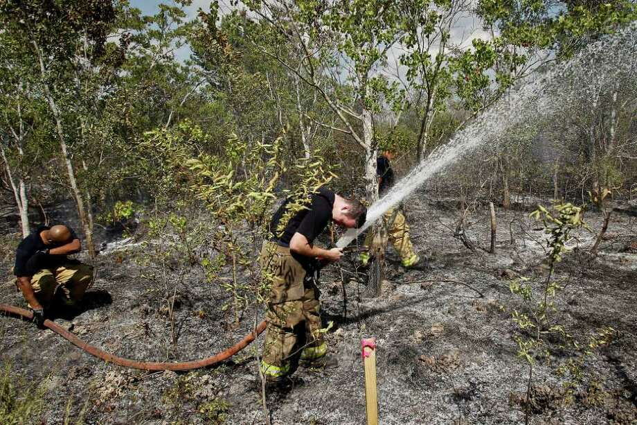 June 14, 2011 | Firefighters try to cool off after hauling extra hoses into a heavily wooded area that toughened the firefighting effort of a large brush fire near Sam Houston Tollway and Mykawa Rd in South Houston. Photo: Michael Paulsen, Houston Chronicle / © 2011 Houston Chronicle