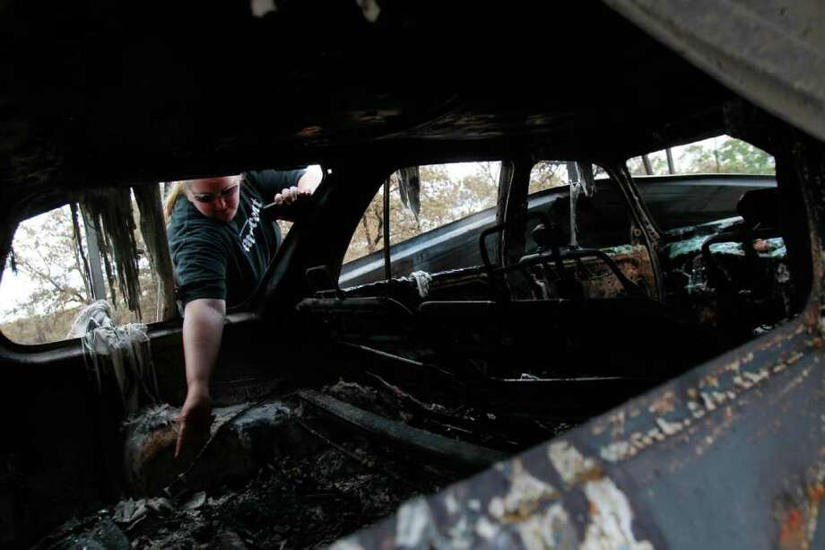 June 24, 2011 | April Gensemer looks inside her destroyed vehicle that was parked in her father's garage, which was destroyed by the wildfire along Millstone Dr. in Grimes County, south of Stoneham, TX. Thirty homes were confirmed destroyed, along with three businesses. Photo: Mayra Beltran, Chronicle / © 2011 Houston Chronicle