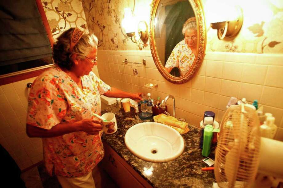 "Aug. 9, 2011 | Lori Sevier grabs a bottle of water to brush her teeth at her home as she refuses to use the salty cloudy city water with a foul smell in Robert Lee. City officials are asking residents to boil the city water before drinking it and some residents, like Sevier, refuse to drink the salty cloudy water.  ""I love this town, but it's going to pots,"" she said.  ""I have to go by water once or twice a week so I can make coffee or beans."" Photo: Michael Paulsen, Houston Chronicle / © 2011 Houston Chronicle"