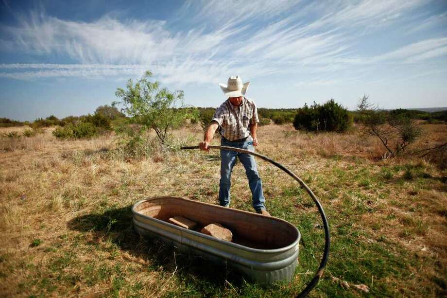 Aug. 9, 2011 | Rancher Lee Hortenstine checks a water trough on his ranch as the temperature toped out at 110 degrees in Robert Lee. Photo: Michael Paulsen, Houston Chronicle / © 2011 Houston Chronicle