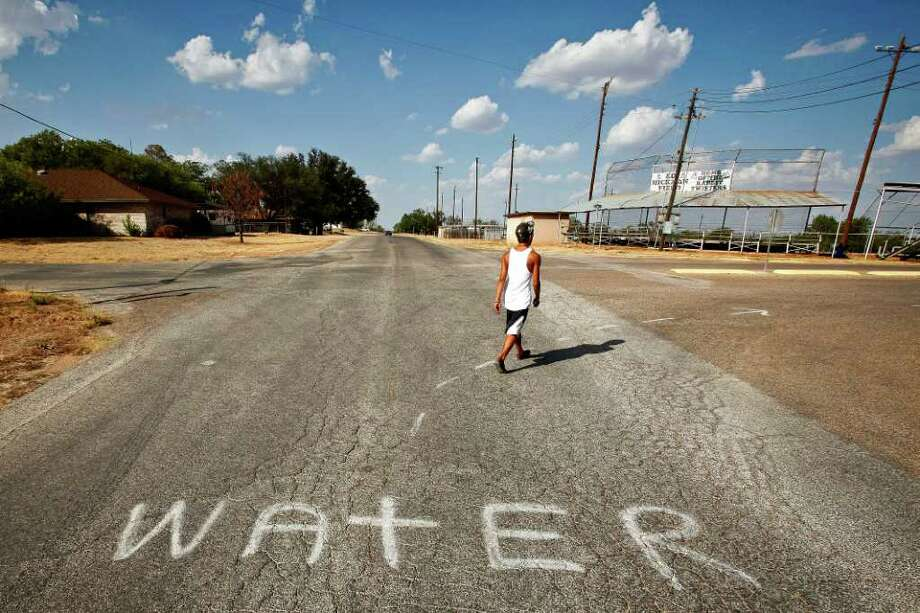 Aug. 9, 2011 | Jesus Landeros, 14, walks to the city pool and past a spray painted sign directing firefighters to a water source to fill their tankers while fighting the recent Wildcat Fire that threatened the town and burnt 160,000 acres in Robert Lee. The city's pool was recently used by a firefighting helicopter when it scooped several hundred gallons to be dropped on a nearby wildfire that threatened the town and burnt 160,000 acres. Photo: Michael Paulsen, Houston Chronicle / © 2011 Houston Chronicle