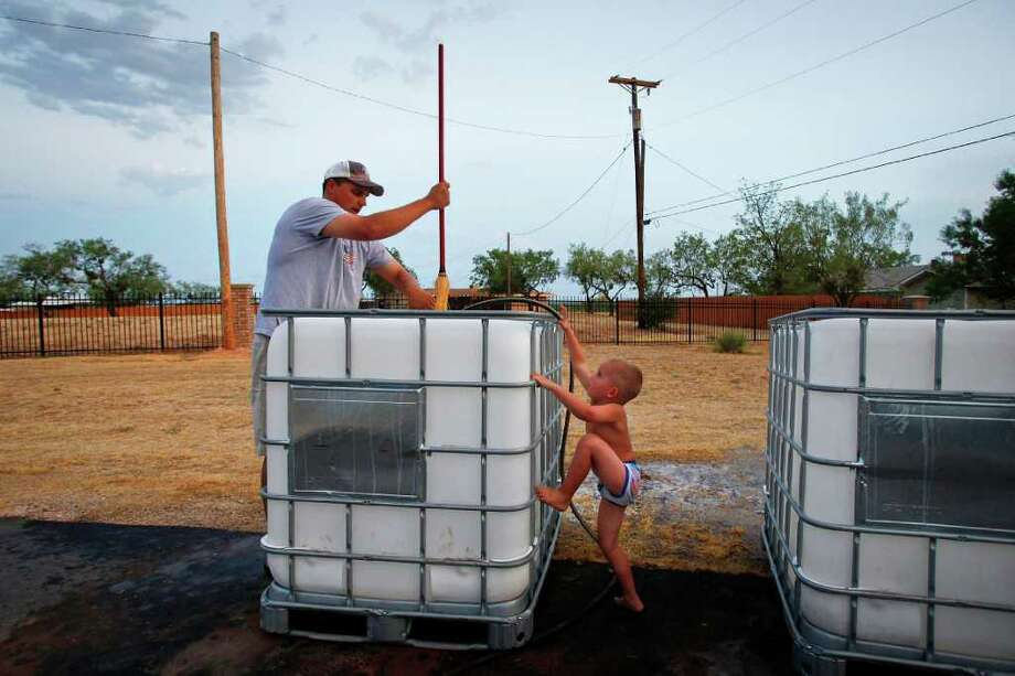 Aug. 9, 2011 | Brennen Hood, 3, tries to help his father, School Superintendent and Athletic Director for Robert Lee High School, Aaron Hood, as he cleans out large chemical containers which will be used as water hauling tanks, at his home in Robert Lee. Each tank holds nearly 250 gallons of water and residents of Robert Lee are forced to drive to neighboring cities to find water to be used for watering lawns and trees. Photo: Michael Paulsen, Houston Chronicle / © 2011 Houston Chronicle