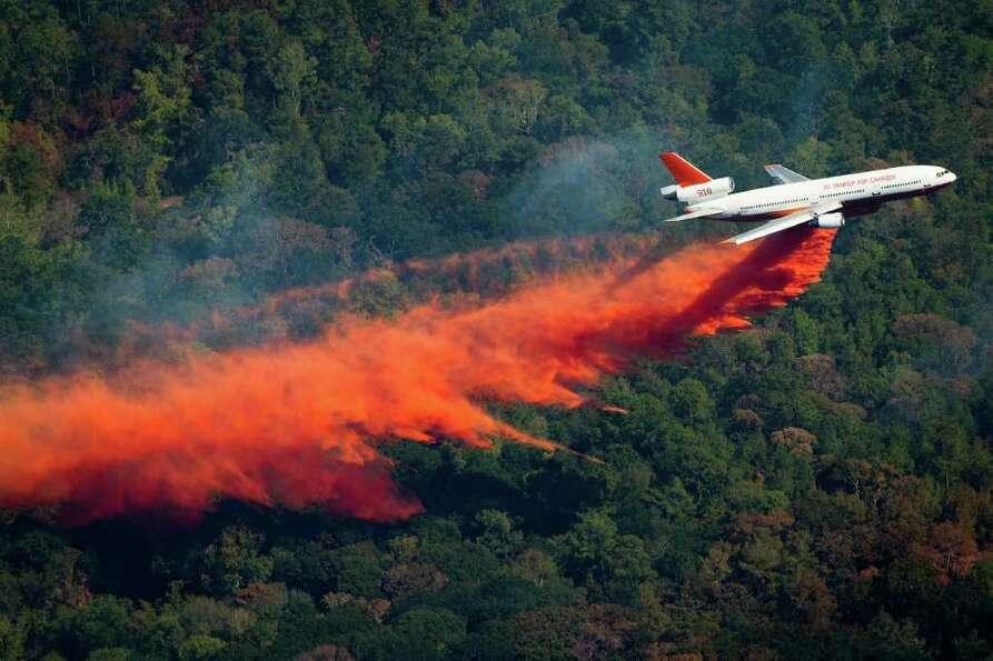 Sept. 10, 2011 | An airplane drops retardant to help fight a large wildfire near Magnolia, Texas. Th