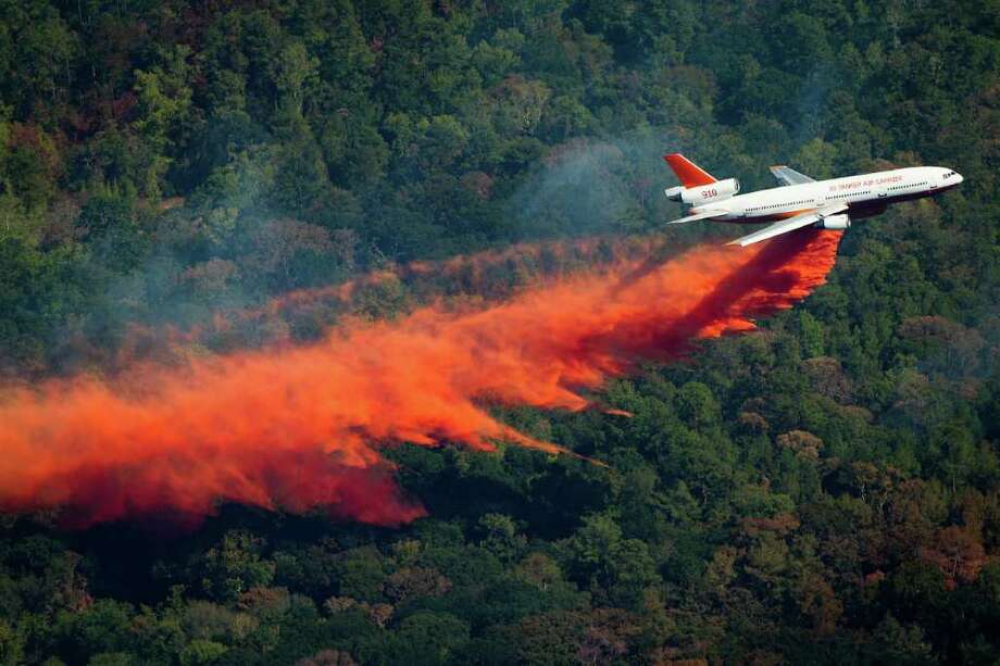 "Sept. 10, 2011 | An airplane drops retardant to help fight a large wildfire near Magnolia, Texas. The plane, a converted DC-10 jet is capable of dropping 12,000 gallons of fire retardant. was assigned to Bastrop County in Central Texas  but was temporarily diverted to attack a ""particularly aggressive fire"" that has been burning across Montgomery, Grimes and Waller counties, said Carman Apple, Texas Forest Service spokeswoman. Photo: Smiley N. Pool, Houston Chronicle / © 2011  Houston Chronicle"