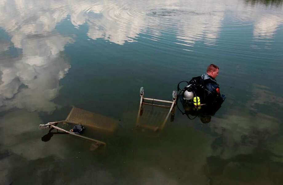 Sept. 20, 2011 | Houston Police Marine Unit Diver Eric Therkildsen wades in the water while he waits for his colleague to complete search for submerged vehicles in a lake off the 10000 block of Windmill Lakes Blvd. in Houston.  Water is receding in lakes due to the drought and objects are resurfacing allowing police to recover stolen items. Photo: Mayra Beltran, Houston Chronicle / © 2011 Houston Chronicle