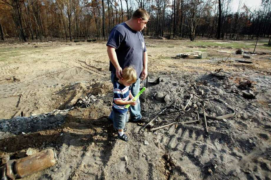 Sept. 29, 2011 | Tri-County Volunteer firefighter Jerry Robertson and his two-year-old son, Garrett, walk through the ashes of what used to be their home in Remington Forest in Magnolia. Robertson's house burned down during the massive wildfires that consumed Waller County earlier this month. Robertson was fighting to save other people's homes as his house went up in flames. Photo: Karen Warren, Houston Chronicle / © 2011 Houston Chronicle
