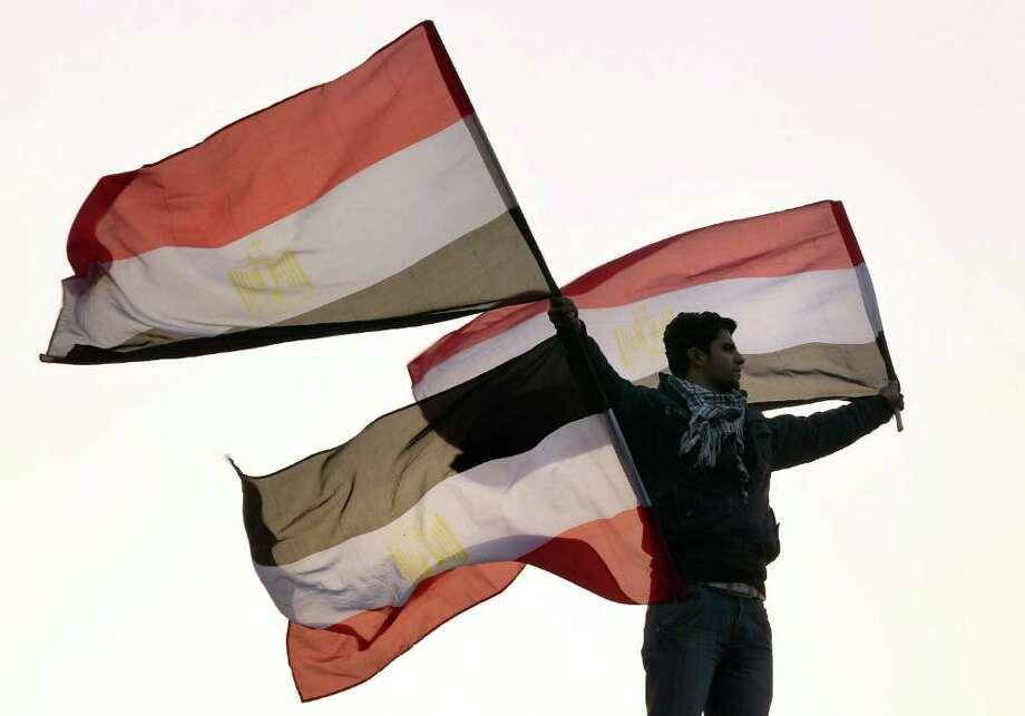 En El Cairo, un joven ondea una bandera egipcia desde un poste de luz en la Plaza Tahrir el 1 de febrero de 2011. Photo: Peter Macdiarmid / Getty Images Europe
