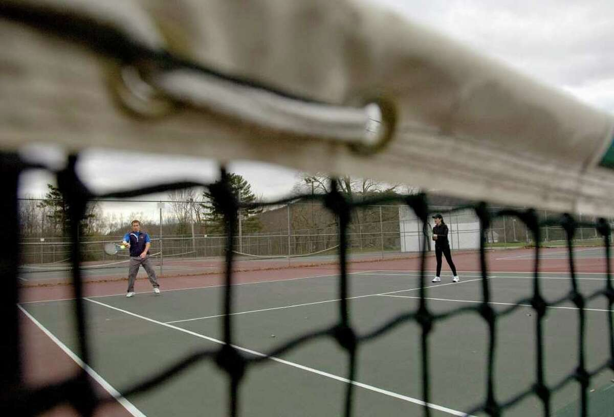 Andrei Paschenko, left, of Danbury, returns the ball as his teammate, Cynthia Wolchuk, of Newtown, watches during a tennis game at Rogers Park in Danbury on Thursday, Dec. 22, 2011.