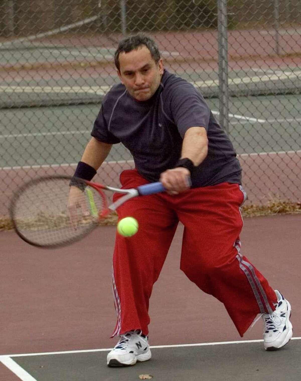 Thomas Perri, of Danbury, returns the tennis ball. Photographed on Thursday, Dec. 22, 2011.