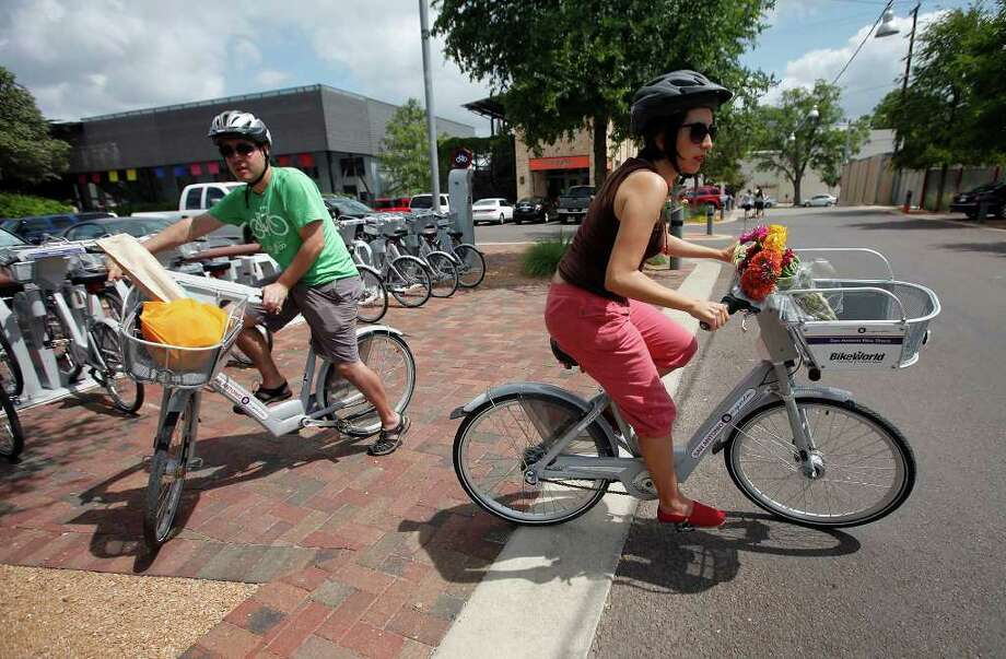 Claudia Zarazua, right, and Ruben Mancha grab bikes from a kiosk in San Antonio. The couple got rid of their car two years ago and regularly use the bikes. Photo: KIN MAN HUI / San Antonio Express-News