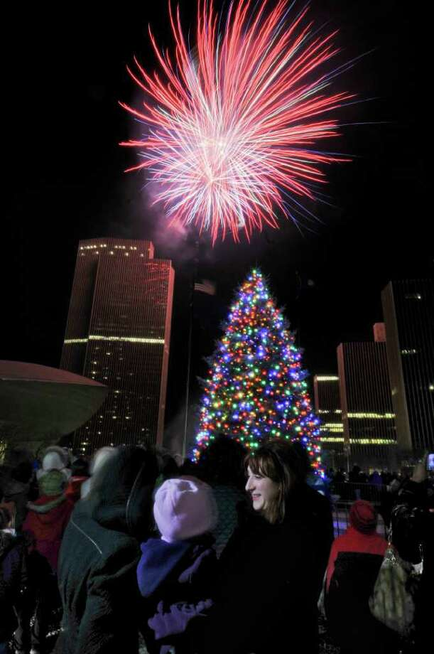 Lori Reginelli of Delmar holds Lexis, 4, the daughter of her friend Tabitha Harting of East Greenbush, left, while watching the annual Christmas tree lighting ceremony and fireworks at the Empire State Plaza on Sunday evening Dec. 4, 2011 in Albany, NY. (Philip Kamrass / Times Union ) Photo: Philip Kamrass / 00015663A