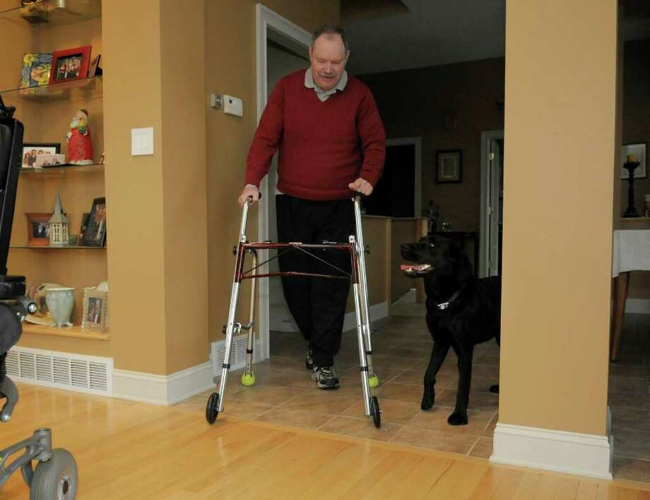 James Nolan uses a walker as he makes his way into the living room with his dog Laddie at his home on Tuesday, Dec. 6, 2011 in Greenwich, NY.  Nolan broke his neck is a bike accident and his good friend, Lee Weiser, trained the black lab puppy and gave the dog to Nolan.  Weiser died of cancer this year.  (Paul Buckowski / Times Union) Photo: Paul Buckowski / 00015650A