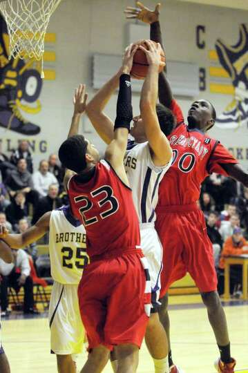 CBA's Joe Krong drives to the basket defended by Schenectady's Danssel Rodriguez and Darius Macon du