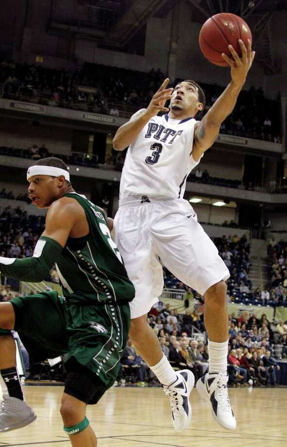 Pittsburgh's Cameron Wright (3) goes in for a layup behind Wagner's Latif Rivers in the first half of the NCAA college basketball game on Friday, Dec. 23, 2011, in Pittsburgh. (AP Photo/Keith Srakocic) Photo: Keith Srakocic