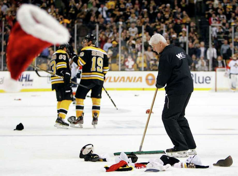MICHAEL DWYER: ASSOCIATED PRESS HOLIDAY HAT TRICK: A TD Garden worker clears the ice after the Bruins' Brad Marchand, left, scored his third goal of the game Friday night against the Panthers. Photo: Michael Dwyer / AP