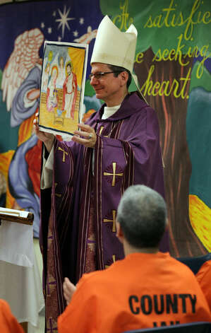 San Antonio Archbishop Gustavo Garcia-Siller holds up a painting on a hankerchief painted by Gabriel Castillo.  The Archbishop celebrated Mass inside Bexar County Jail as a way of ministering to inmates unable to attend a service with their families.  Friday, Dec. 23, 2011. Photo Bob Owen/rowen@express-news.net