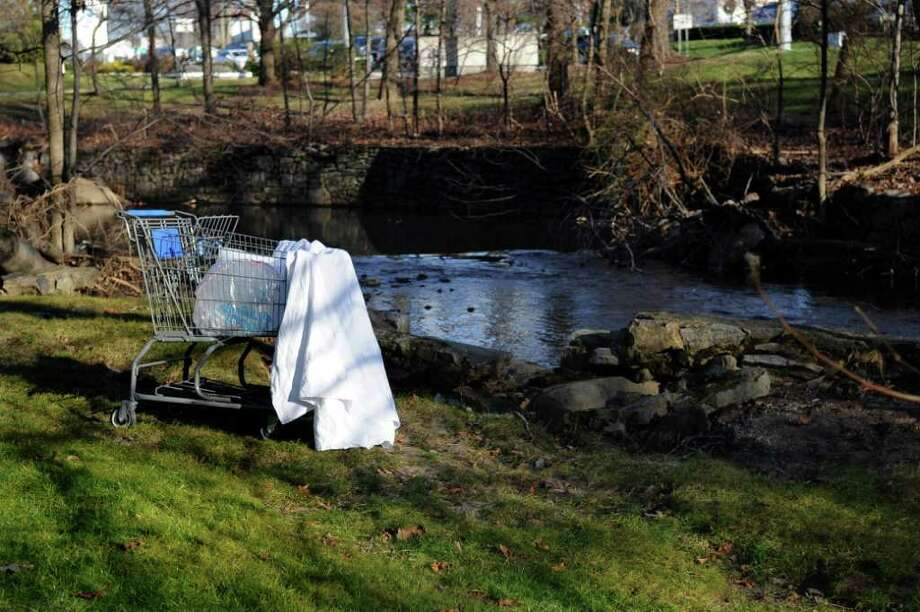 A shopping cart sits on the bank of a stream beside Connecticut Ave. in Norwalk where a reportetly homeless man had a medical emergency and died. His body was recovered from the stream Saturday afternoon. Photo: Lindsay Niegelberg / Stamford Advocate