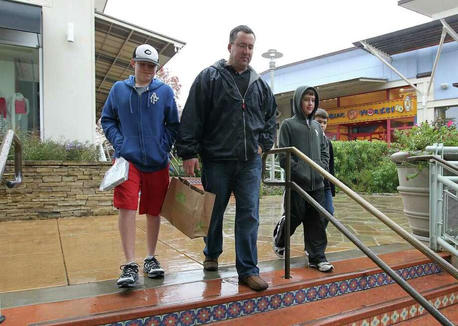 Chris Connaughton leads his sons Collin (from left), Sean and Cade around The Shops at La Cantera on Saturday, Dec. 24, 2011 to get last minute gifts on Christmas eve. Kin Man Hui/kmhui@express-news.net Photo: Kin Man Hui, SAN ANTONIO EXPRESS-NEWS / San Antonio Express-News