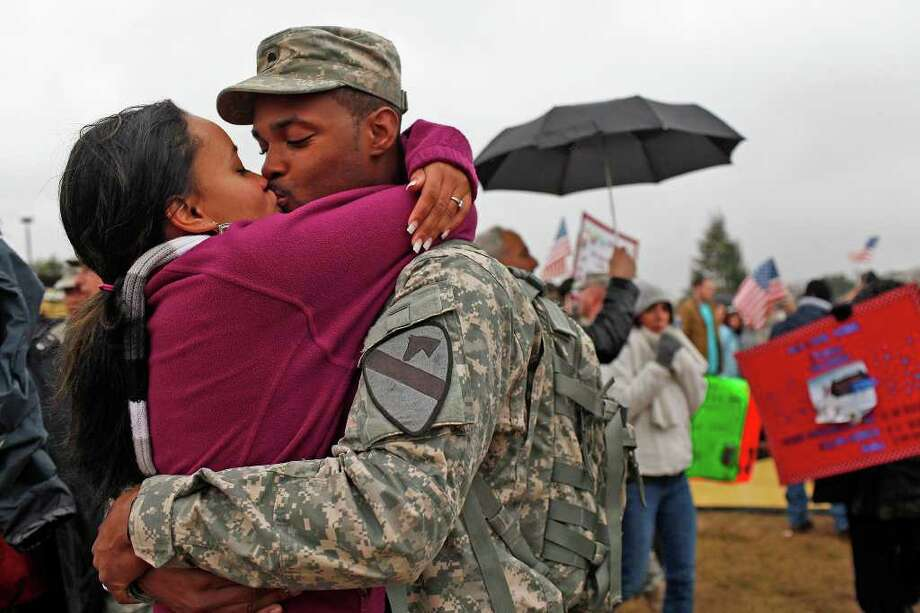 Specialist Chris Wimberly kisses his wife, Shaelyn Wimberly, upon reuniting with her at the conclusion of the homecoming ceremony for soldiers returning home from Iraq at Fort Hood on Saturday, Dec. 24, 2011. Photo: LISA KRANTZ, SAN ANTONIO EXPRESS-NEWS / SAN ANTONIO EXPRESS-NEWS