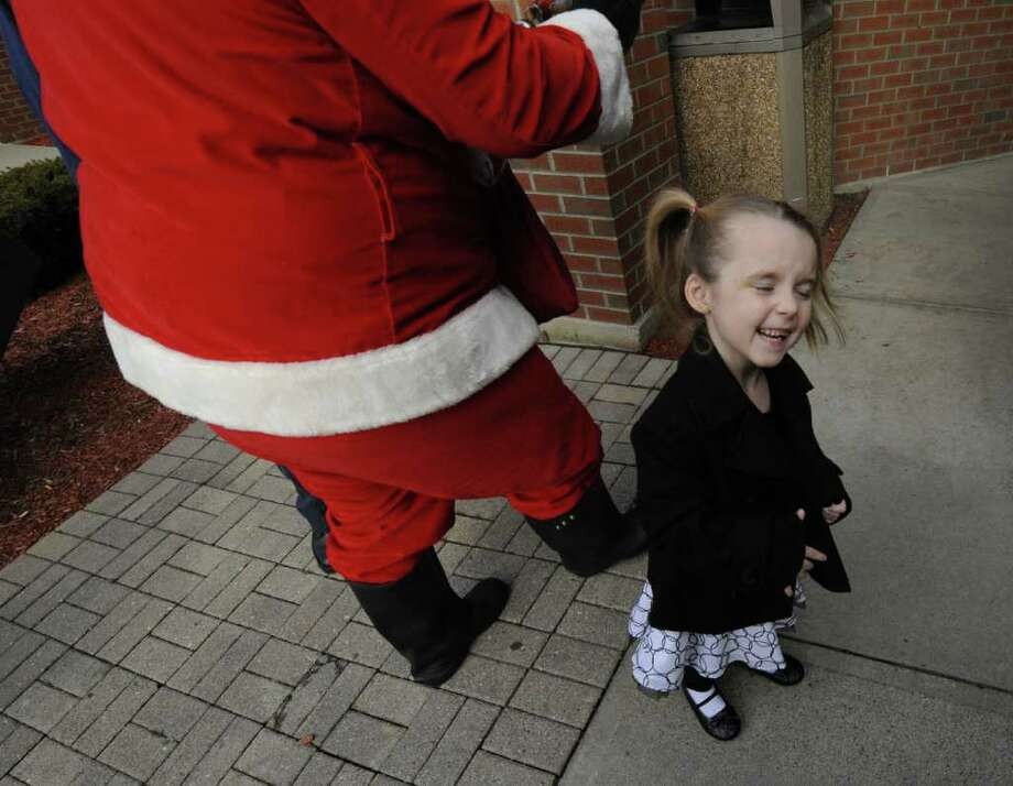 Santa arrives at the Residence Inn in East Greenbush, N.Y. with the aid of a fire engine from Clinton Heights Fire Company Dec. 24, 2011 to deliver gifts to a family that was displaced from their home after a fire on Dec. 12th. One of those family members, four year old Madison Bell shows her excitement at the arrival of the man in red. (Skip Dickstein/Times Union) Photo: Skip Dickstein / 00015858A