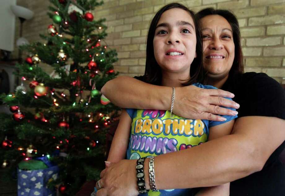 Barbara Gutierrez holds her 10 year old daughter Destinee Starr Fernandez (cq) by their Christmas tree in their apartment. Gutierrez had to spend a year away from her kids, serving time and getting clean. Thursday, Dec. 24, 2011. Photo Bob Owen/rowen@express-news.net Photo: BOB OWEN, SAN ANTONIO EXPRESS-NEWS / rowen@express-news.net