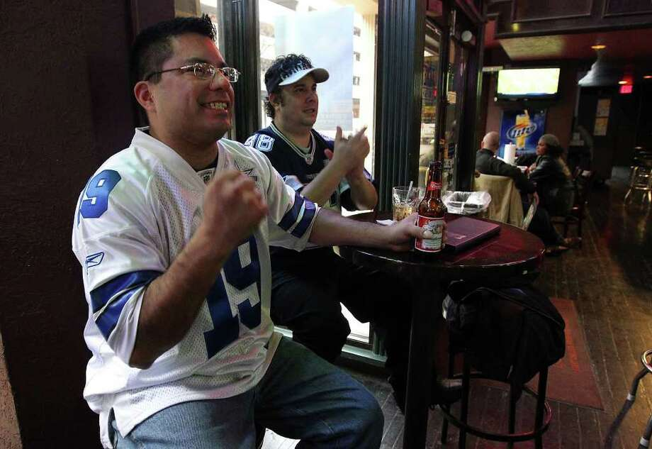 Cowboys fans Paul Chavez (left) and Allen Wilke react while watching the Cowboys play the Philadelphia Eagles on Saturday, Dec. 24, 2011 at the Ticket Sports Pub in downtown San Antonio. A mix of fans were present to watch the various games including the Cowboys game on Christmas Eve. Photo: KIN MAN HUI, SAN ANTONIO EXPRESS-NEWS / SAN ANTONIO EXPRESS-NEWS
