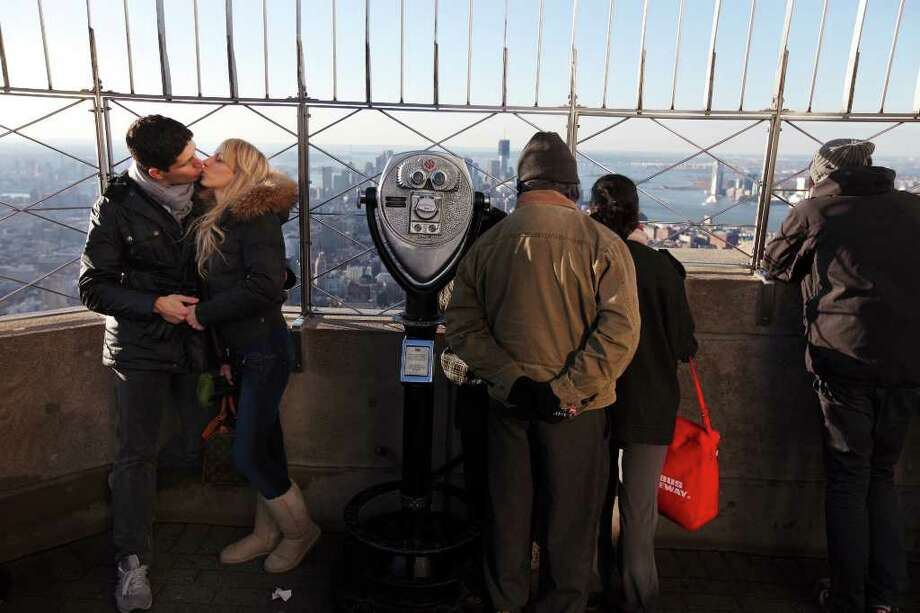 CHANG W. LEE : NEW YORK TIMES HOT SPOT: A couple kiss on the observatory deck of the Empire State Building in New York on Christmas Eve. Four million people visit the building's observation decks each year. Photo: CHANG W. LEE / NYTNS