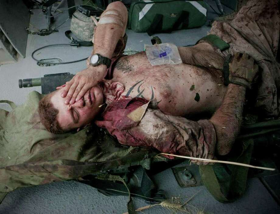 ANJA NIEDRINGHAUS PHOTOS : ASSOCIATED PRESS WOUNDED IN JUNE: Marine Cpl. Burness Britt lies inside a medevac helicopter after being hit by shrapnel in Afghanistan. Photo: Anja Niedringhaus / AP